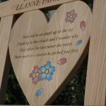 Close up of heart shaped center panel with text engraving and flower resin inlays