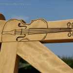 Close up of a violin engraving which perfectly follows the shape of a top rail