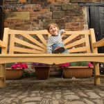 Little boy sat on a sunshine bench