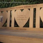 Memorial bench with two heart shaped panels. each with an inlay of cuddly toys