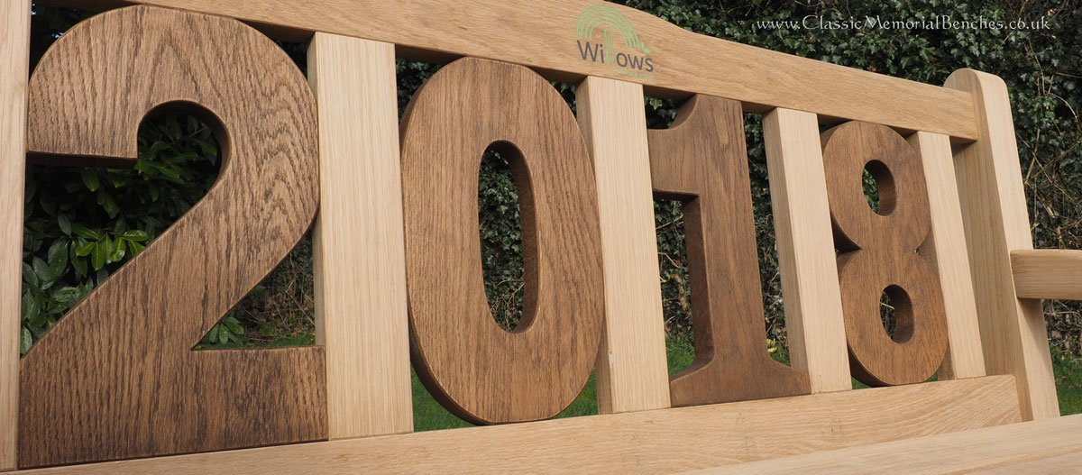 Close up of the back of a bench whose back panels are in the shape '2018'
