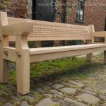 Chunky oak bench with a large back panel with a large inscription