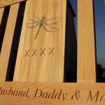 Close up of an iroko memorial bench with a resin inlay of a dragonfly