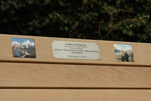 Two photo plaques and an engraved plaque on a memorial bench
