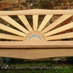 Iroko bench with a sunset shaped back panel engraved with a rainbow