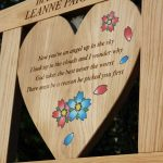 Close up of a heart shaped center panel engraved with a poem and flower resin inlays