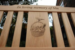 Oak memorial bench with a center panel engraved with a bird perched on a basket full of vegetables