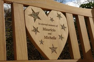 Heart shaped center panel of a memorial bench engraved with words and stars, which are filled with shiny stones
