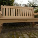 Iroko memorial bench with word engravings on the top and front rails