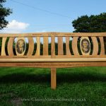 Iroko memorial bench with two photo carvings and word engraving on the top ad front rails