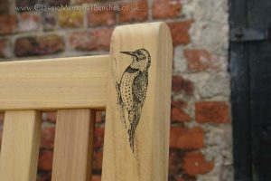 Close up of the top corner of a bench with an engraving of a woodpecker