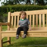 A little boy smiling while sitting on a memorial bench