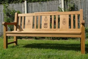 An iroko memorial bench with three engraved back panels