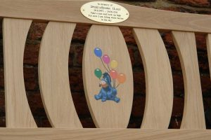 Oak memorial bench with a gold oval plaque and a center panel with a resin inlay of Eeyore from Winnie the Pooh holding balloons