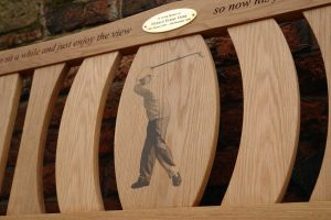 Iroko memorial bench with a gold oval plaque and a photo carving of a man playing golf on the center panel