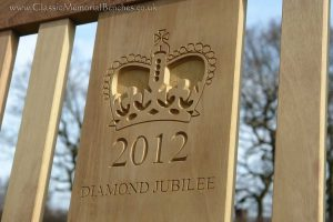 A close up of a 2012 Diamond Jubilee commemorative bench with an engraving of a crown