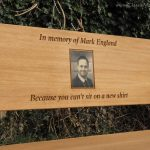Iroko memorial bench with a square photo carving of a man smiling