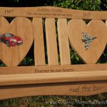 Iroko memorial bench with two heart shaped back panels and two resin inlays, one a car and the other a fighter jet