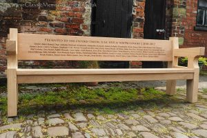 An oak bench with a large back rail engraved with several names for the Oxford Union