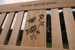 Oak bench with a top rail engraving and a center panel engraved with detailed flowers and a bee