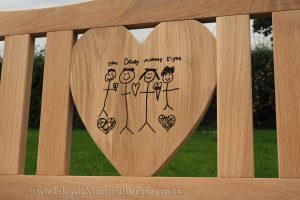 Heart shaped center panel with an engraving of a childs drawing of their family