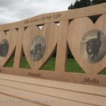 Bench with three heart shaped panels with photo engravings of dogs on